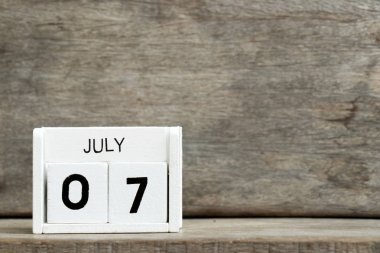 White block calendar present date 7 and month July on wood background