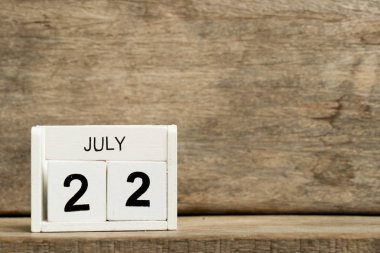 White block calendar present date 22 and month July on wood background