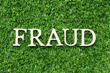 Wood alphabet letter in word fraud on green grass background