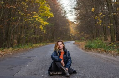 Young beautiful girl with long hair sitting on the asphalt road in the autumn forest