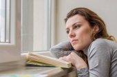 junge charmante Studentin, mit langen Haaren, traurig am Fenster Lesebuch mit Unterricht