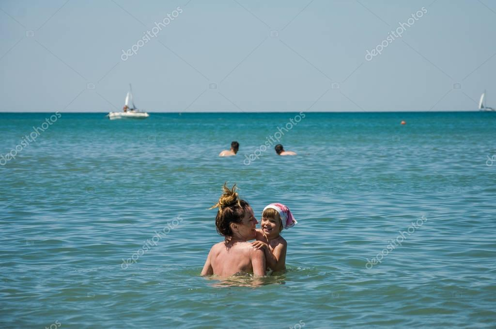 Young beautiful mother with her charming daughter bathes in the Tyrrhenian Sea on a bright sunny afternoon, happy family