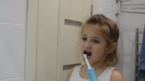 Girl child brushes her teeth with an electric toothbrush