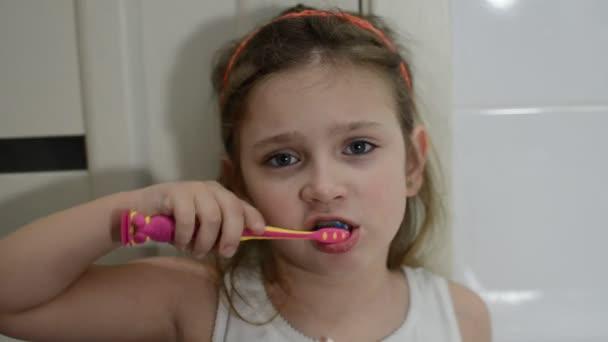 Malá okouzlující holčička čištění zubů v koupelně