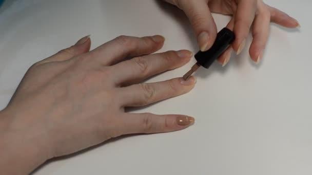 Žena maluje nehty s béžovou lak na nehty při manikúře