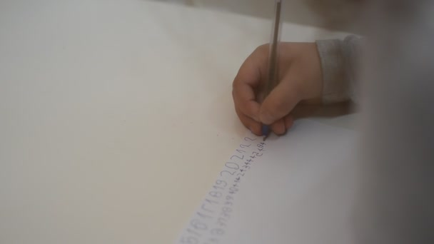 Little girl kid learn to write with numbers pen on a piece of paper