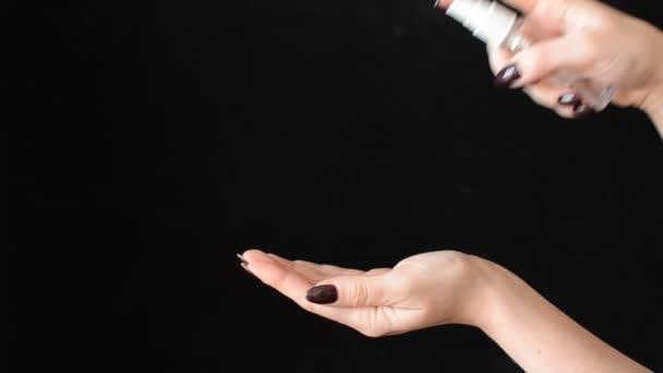 Nő spray antibakteriális fertőtlenítő a kezét egy fekete háttér