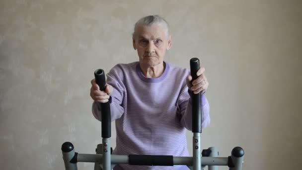 Eine ältere Frau sitzt zu Hause im Sportsimulator