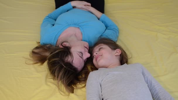 Fun and happiness of mother and daughter in bed, happy family