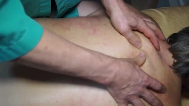 Mužské ruce lékaře se léčebné masáže na zadní straně ženy. Profesionální techniky fungují na svaly zad, relaxaci, lámání spouštěcí body