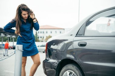 sad woman standing near car with scratch