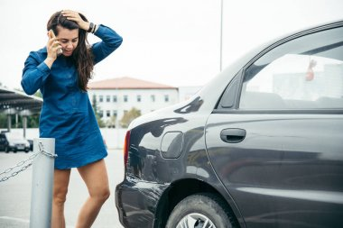 sad woman standing near car with scratch