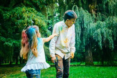 father with daughter play in park with holi paints