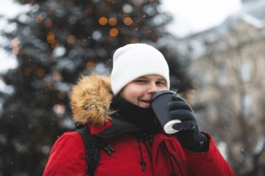 man outdoors drinking coffee from paper cup winter time warm up red coat