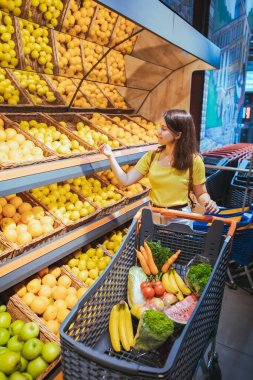 woman taking oranges from supermarket store shelf shopping concept