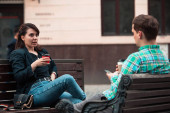smiling couple sitting on bench talking to each other drinking coffee. friends urban life