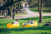 couple laying on yellow inflatable mattress in city park. reading book. surfing phone. leisure time
