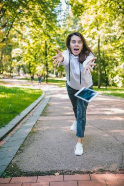 young woman let down mobile phone on stone ground. accident drop of smartphone