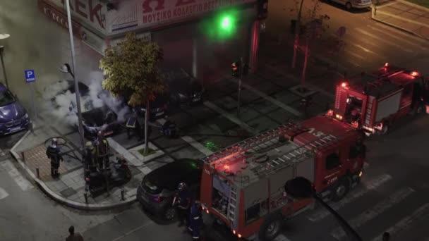 Soluň, Řecko - 16. prosince 2019: Řečtí hasiči při požáru v luxusním autosalonu. Zvýšený pohled na helénské hasičské vozy  hasiči v uniformě během nočního požáru města.