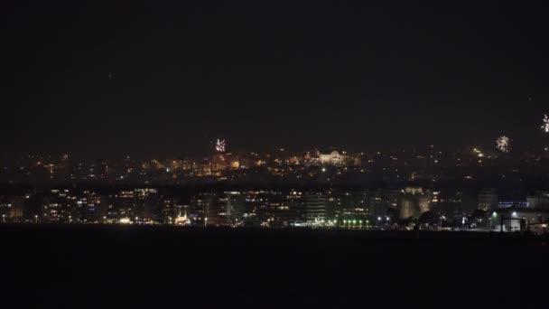 Řada ohňostrojů nad velkou obytnou krajinou v noci. Silvestr 01 Leden 2020 pyrotechnika v Soluni, Řecko pro nadcházející Nový rok, vidět z nábřeží.