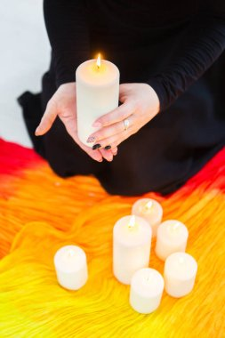 Female hands hold a lighted candle. A fortune teller performs a magical. Ritual of enchantment and clairvoyance. Seance and prediction of the future