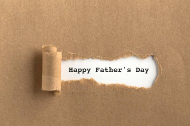 The text  behind torn brown paper