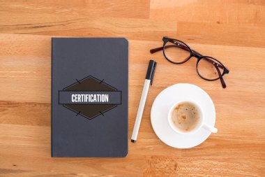 Book, coffee cup, glasses on desk