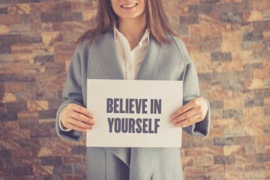 Woman presenting BELIEVE IN YOURSELF CONCEPT