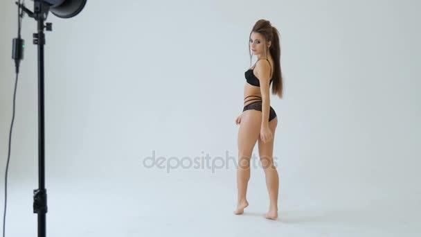 Beautiful girl in black lace lingerie dances in white studio. Slow motion