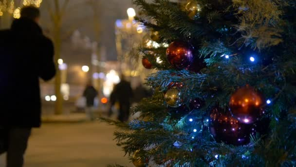Weihnachtsschmuck Kugeln hängen am Baum auf dem Hintergrund Lichtergirlanden
