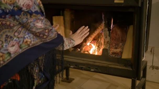 Domácí pohodlí. Žena, ohřívá ruce k ohni. Teplo v zimě