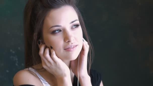Krásná mladá dívka tančí na hudbu. Používejte sluchátka. Pomalu se v čase s hudbou