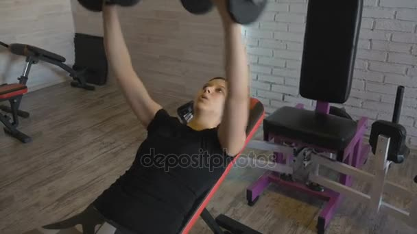 Mladá dívka je cvičení s činka v posilovně