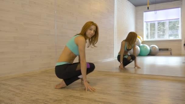 Sexy žena, která dělá protahovací cvičení v tělocvičně.