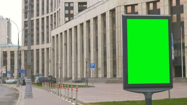 egy óriásplakát, egy zöld képernyő-ra egy elfoglalt utca.