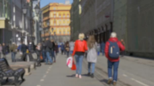 Blurred intentionally, people are walking along the beautiful streets of the city. A beautiful sunny day