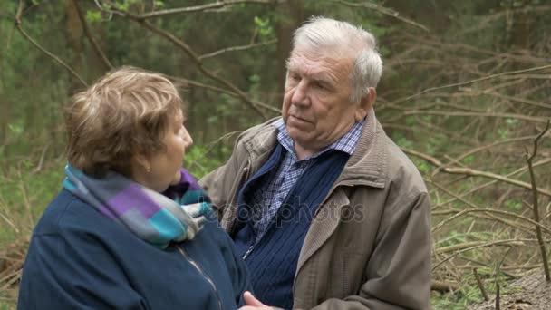 ein älteres, schönes Paar, das in einem Wald auf einem gesägten Holz sitzt. sie reden zärtlich, umarmen sich, schauen einander verliebt an. Gute Stimmung.