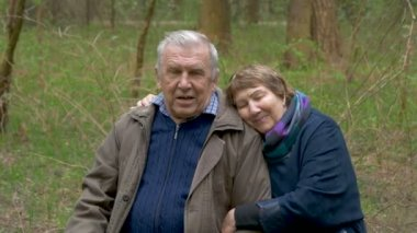 An elderly, beautiful couple sitting in a wood, on a sawn wood. They tenderly talk, hug, in love look at each other. Good mood.