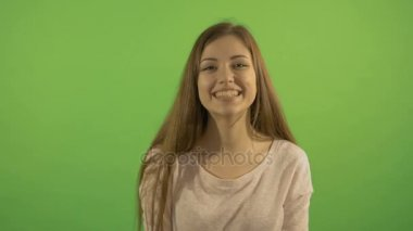 Portrait of a beautiful girl who smiles and laughs. On the background of a green screen.