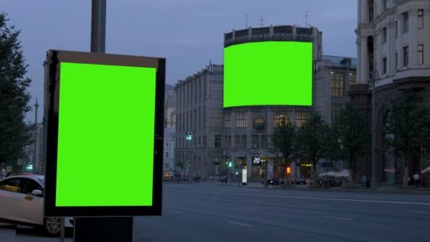Dva billboardy s zeleným plátnem. Večer, na rušné ulici.