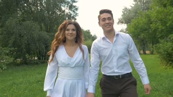 Fiatal gyönyörű pár séta a parkban. Romantikus dátum. Boldogok, nevetett, és néztek egymásra.
