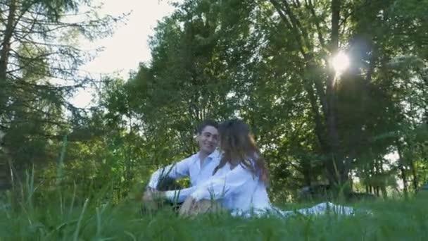 A fehér ruha gyönyörű pár ül a zöld fű. Siess, gyengédség és szeretet.