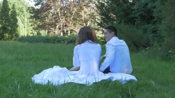 Romantikus pár fehér ruhát ölelés, és csók a dátumot. Ők ülnek a zöld fűben, egy gyönyörű Park.