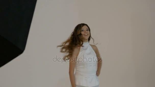 Junge Frau in einem weißen Anzug ist in einer Foto-Session teilnehmen.