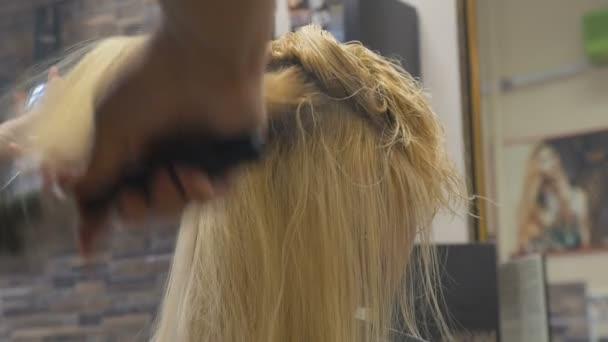 Fodrász fodrász lépek a haját, hogy egy szőke nő egy hajszárító segítségével