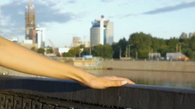 A womans hand slides along the railing of the embankment.