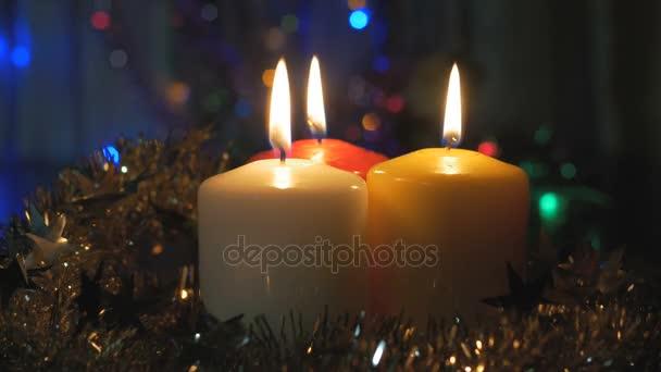 Nová let svíčky detail a vánoční ozdoby. Rozmazané pozadí s barevnými světly.