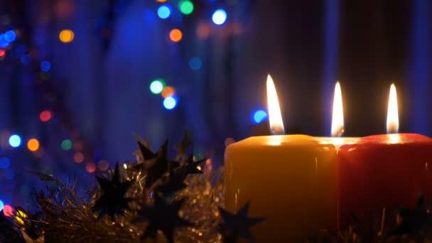 Nová let svíčky a vánoční ozdoby. Rozmazané pozadí s barevnými světly. Pohyb kamery je blíže k objektu