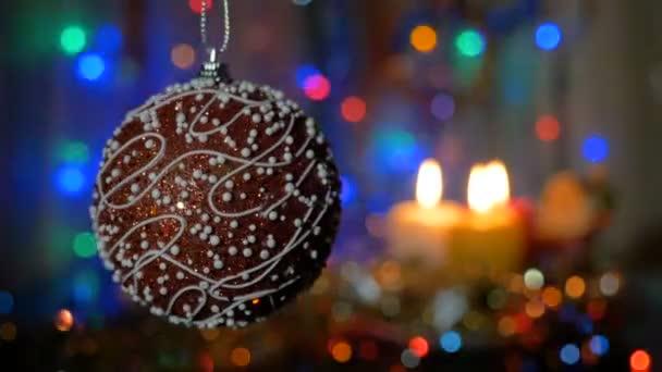 Krásný červený míček. Silvestrovské a vánoční dekorace. Hořící svíčky. Blikající girlandy. Rozmazané pozadí