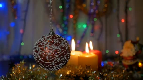 Una bella palla rossa ruota in primo piano. Decorazioni di Natale e Capodanno. Candela Burning. Ghirlande di lampeggiare. Priorità bassa vaga